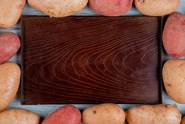 Widok Z Góry Rudych I Czerwonych Ziemniaków Ustawionych W Kwadratowy Kształt Wokół Pustej Tacy Na Drewnianej Powierzchni Darmowe Zdjęcia