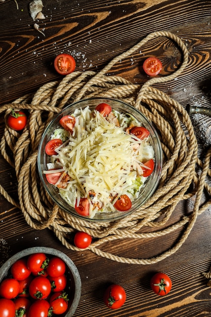 Widok Z Góry Sałatka Cezar Z Pomidorkami Cherry W Misce Z Liny Na Stole Darmowe Zdjęcia