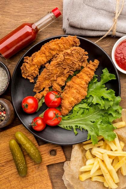 Widok Z Góry Smażony Kurczak Z Pomidorami I Sałatką Na Talerzu Z Frytkami Darmowe Zdjęcia