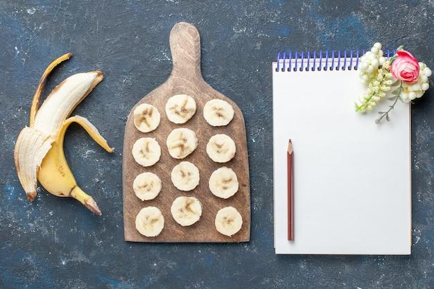 Widok Z Góry świeżego żółtego Banana Słodkiego I Pysznego, Obrane I Pokrojone W Plasterki Na Ciemnych, Owocowych Jagodowych Słodkich Witaminach Darmowe Zdjęcia