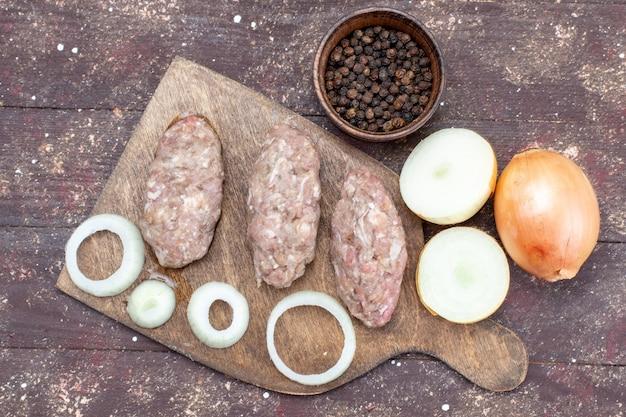 Widok Z Góry świeżej Cebuli W Całości I Pokrojonej W Plastry Z Surowego Mięsa Na Brązowym, Roślinnym Produkcie Jako Składnik żywności Darmowe Zdjęcia