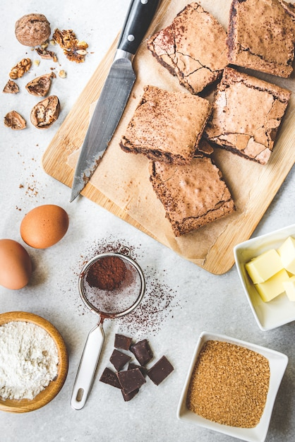 Widok Z Góry świeżo Upieczonego Domowego Ciasta Brownie Ułożonego Ze Składników Przepisu Na Biały Rustykalny. Premium Zdjęcia