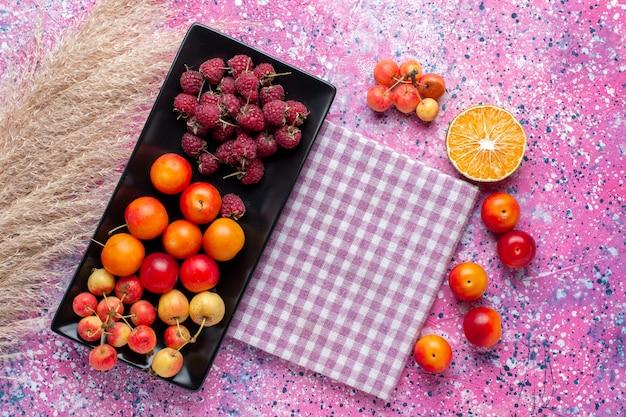 Widok Z Góry świeżych Owoców Malin I śliwek Wewnątrz Czarnej Formy Na Różowej Powierzchni Darmowe Zdjęcia