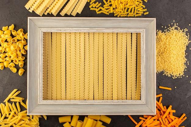 Widok Z Góry Szara Ramka Na Zdjęcia Wraz Z Innym Uformowanym żółtym Surowym Makaronem Na Ciemnym Tle Darmowe Zdjęcia