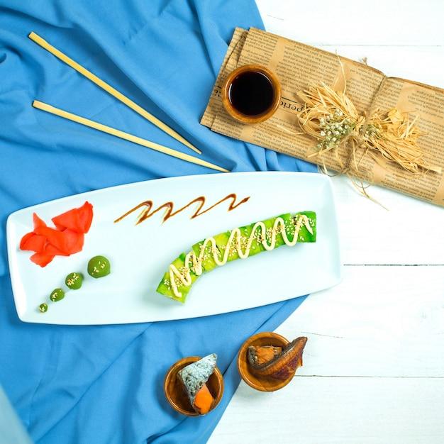 Widok Z Góry Tradycyjnej Japońskiej Bułki Sushi Z Awokado Z Warzywami Z Węgorza Tofu I Zbliżenie Awokado Podawane Z Sosem Sojowym Imbirowym I Wasabi Na Niebiesko-białym Bac Darmowe Zdjęcia