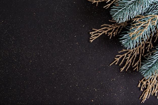 Widok Z Góry Wesołych świąt Czarne Tło Ozdobione Gałęziami Drzewa Szczęśliwego Nowego Roku I Brokatem Z Miejsca Na Kopię. Zimowe święto Dekoracji świątecznej Koncepcji Zabawy, Płaskie Lay. Premium Zdjęcia