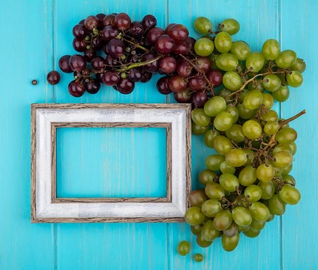 Widok Z Góry Winogron I Ramki Na Niebieskim Tle Z Miejsca Na Kopię Darmowe Zdjęcia