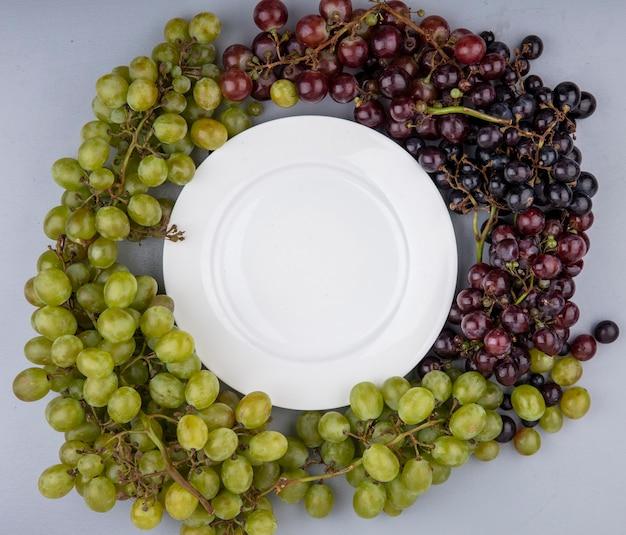 Widok Z Góry Winogron Wokół Płyty Na Szarym Tle Darmowe Zdjęcia