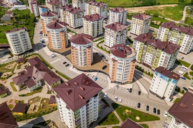 Widok z góry wysokich budynków mieszkalnych lub biurowych, zaparkowanych samochodów, krajobrazu miejskiego miasta. fotografia lotnicza dronów. Premium Zdjęcia