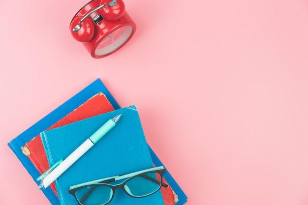 Widok z góry z książek, okularów, zegarów pióra napowietrznych na różowym pastelowym tle, płaskie świeckiej edukacji Premium Zdjęcia