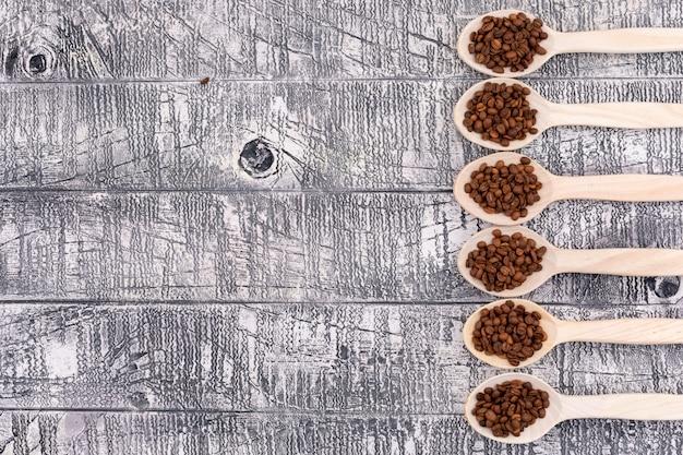 Widok Z Góry Ziaren Kawy W Innej Drewnianej łyżce Na Białej Powierzchni Drewna Darmowe Zdjęcia