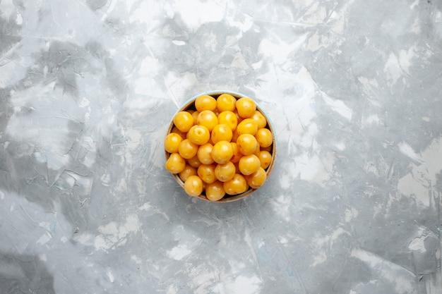 Widok Z Góry żółte Wiśnie Wewnątrz Talerza Na Jasnoszarym Biurku Owoce świeże Letnie Kolorowe Zdjęcie Darmowe Zdjęcia