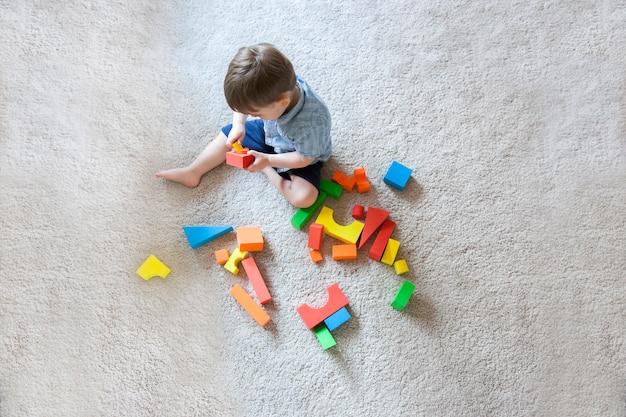 Widok Z Lotu Ptaka Blondynki Dziecko Bawić Się Z Edukacyjnymi Blokowymi Drewnianymi Grami Dla Dzieci. Premium Zdjęcia