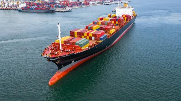 Widok z lotu ptaka kontenerowiec przewożący kontener w logistyce importu eksport i transport międzynarodowy kontenerowcem na otwartym morzu. Premium Zdjęcia
