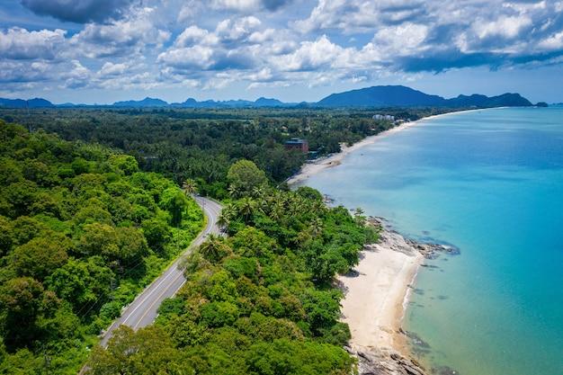 Widok Z Lotu Ptaka Na Drogę Między Palmą Kokosową I Wielkim Oceanem W Ciągu Dnia W Nakhon Si Thammarat, Tajlandia Premium Zdjęcia