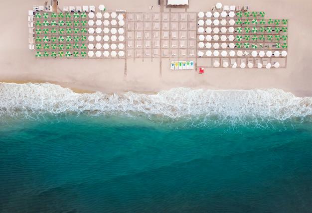 Widok Z Lotu Ptaka Na Niesamowitą Plażę Z Parasolami I Turkusowym Morzem W Ciepłe Lato. Premium Zdjęcia