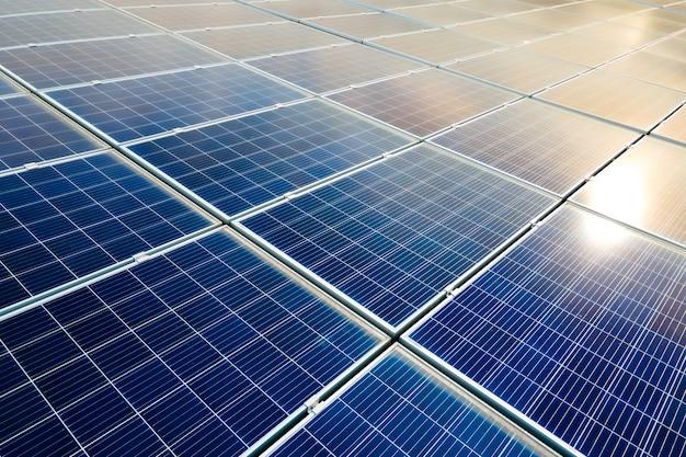 Widok Z Lotu Ptaka Na Powierzchnię Niebieskich Fotowoltaicznych Paneli Słonecznych Zamontowanych Na Dachu Budynku Do Produkcji Czystej Ekologicznej Energii Elektrycznej. Produkcja Koncepcji Energii Odnawialnej. Premium Zdjęcia
