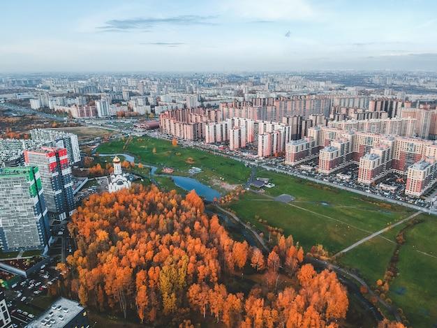 Widok z lotu ptaka na przedmieścia, piękny jesienny park i wieżowiec. sankt petersburg, rosja Premium Zdjęcia