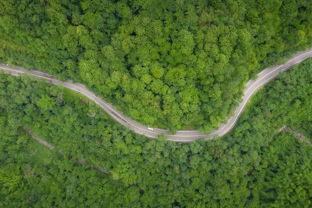 Widok z lotu ptaka nad halną drogą iść przez tropikalnego tropikalnego lasu deszczowego krajobrazu w tajlandia. Premium Zdjęcia
