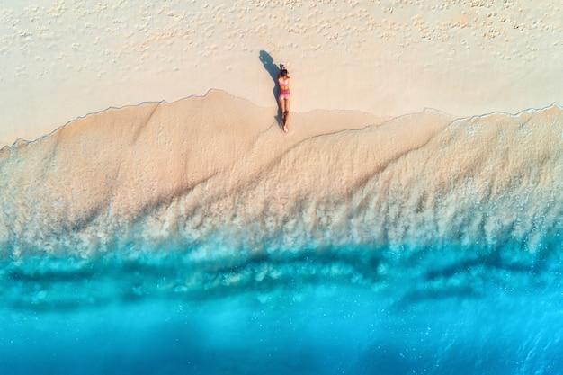 Widok Z Lotu Ptaka Pięknej Młodej Kobiety Leżącej Na Białej, Piaszczystej Plaży W Pobliżu Morza Z Falami O Zachodzie Słońca. Letnie Wakacje. Widok Z Góry Na Sportową Szczupłą Dziewczynę, Czysta Lazurowa Woda. Seksowne Pośladki. Zrelaksować Się Premium Zdjęcia