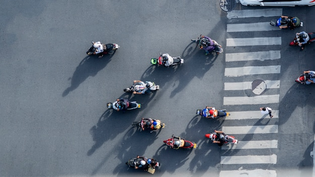 Widok z lotu ptaka rozmycie rowerzystów jeździć na motocyklach, aby przejść pieszych przejście dla pieszych na drodze z sygnalizacją wzór ruchu na ulicy. Premium Zdjęcia