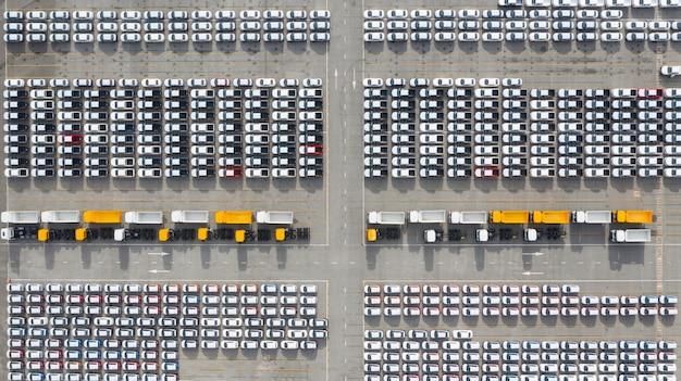 Widok z lotu ptaka terminal eksportu nowych samochodów, nowe samochody czekają na eksport w głębokim porcie morskim. Premium Zdjęcia