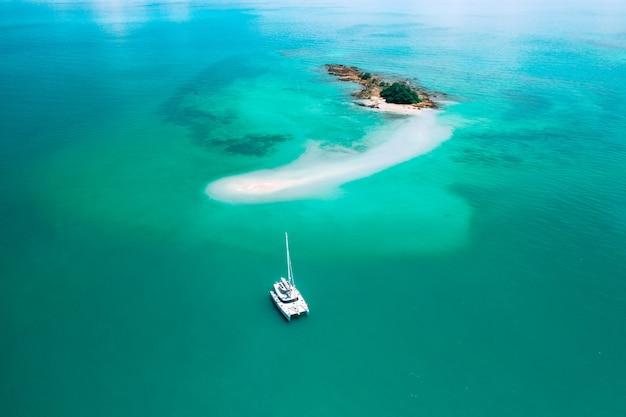 Widok z lotu ptaka żaglowiec zakotwicza na rafie koralowa. widok z lotu ptaka, motyw sportów wodnych. Premium Zdjęcia