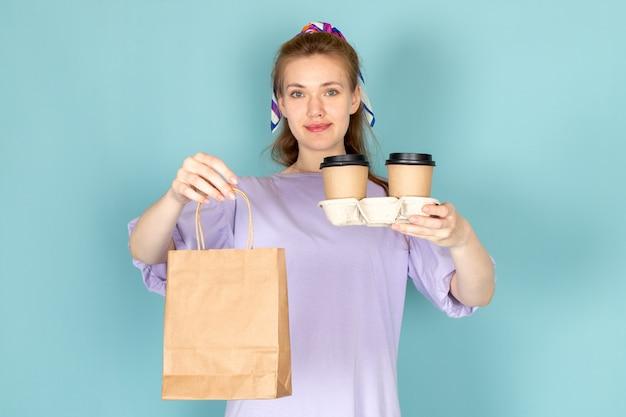Widok Z Przodu Atrakcyjna Kobieta W Niebieskiej Koszuli Trzyma Pakiet Papieru I Filiżanki Kawy Na Niebiesko Darmowe Zdjęcia