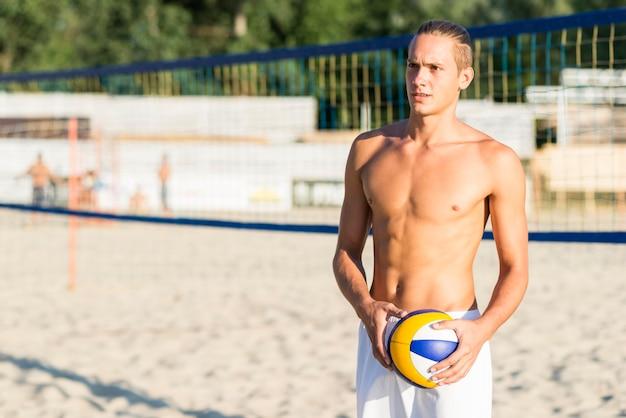 Widok Z Przodu Bez Koszuli Siatkarz Na Plaży Trzymając Piłkę Darmowe Zdjęcia