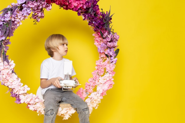 Widok Z Przodu Blond Chłopiec śliczna Urocza Blondynka Z Włosami Siedząca Na Kwiatku Stała Na żółtej Przestrzeni Darmowe Zdjęcia
