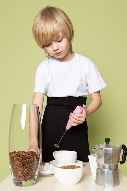 Widok Z Przodu Blondynka Chłopiec Przygotowuje Kawowy Napój Na Stole Na Kamiennej Kolorowej Przestrzeni Darmowe Zdjęcia