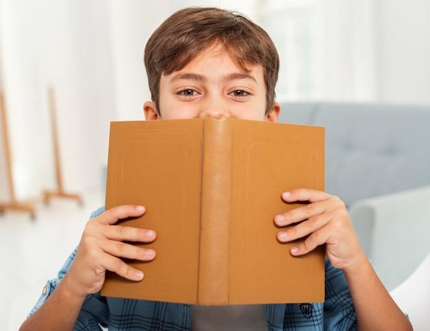 Widok z przodu chłopiec czyta w domu Darmowe Zdjęcia
