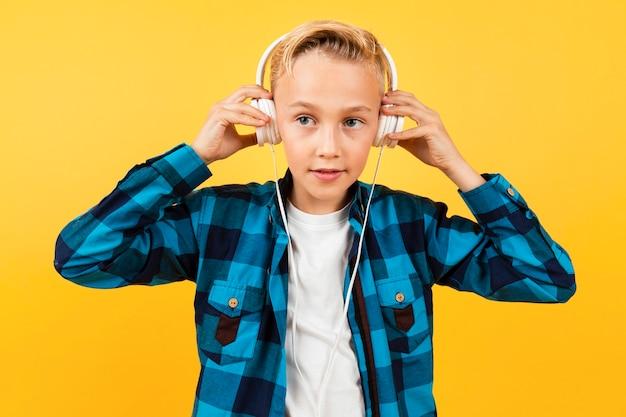 Widok z przodu chłopiec zakładanie słuchawek Darmowe Zdjęcia