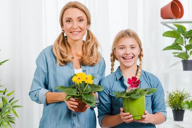 Widok Z Przodu Córka I Mama Trzyma Kwiaty Garnek Darmowe Zdjęcia