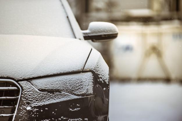 Widok Z Przodu Czarnego Samochodu Pokrytego Cienką Warstwą śniegu Premium Zdjęcia
