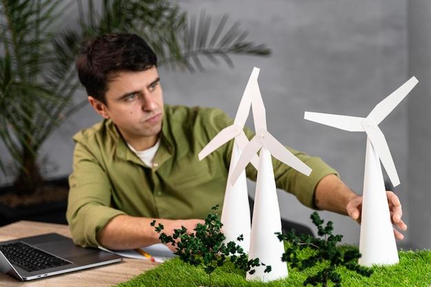 Widok Z Przodu Człowieka Pracującego Nad Projektem Ekologicznej Energii Wiatrowej Z Laptopem I Turbinami Wiatrowymi Darmowe Zdjęcia