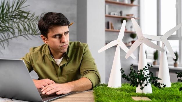 Widok Z Przodu Człowieka Pracującego Nad Projektem Ekologicznej Energii Wiatrowej Z Laptopem Darmowe Zdjęcia