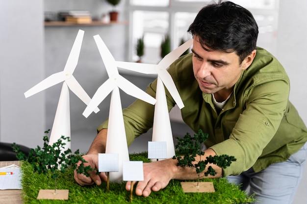 Widok Z Przodu Człowieka Pracującego Nad Projektem Ekologicznej Energii Wiatrowej Z Turbinami Wiatrowymi Darmowe Zdjęcia