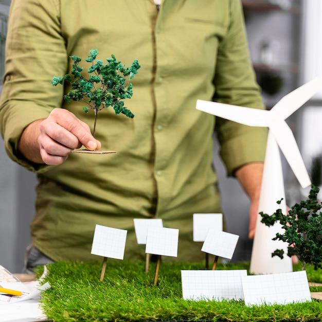 Widok Z Przodu Człowieka Pracującego Nad Układem Projektu Ekologicznej Energii Wiatrowej Z Turbinami Wiatrowymi Premium Zdjęcia