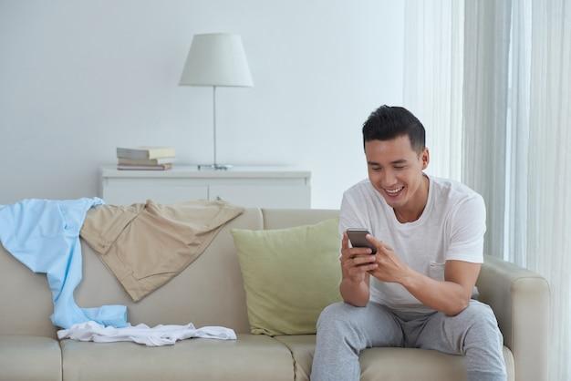 Widok z przodu człowieka sms-y do przyjaciół w domu i uśmiechnięty Darmowe Zdjęcia