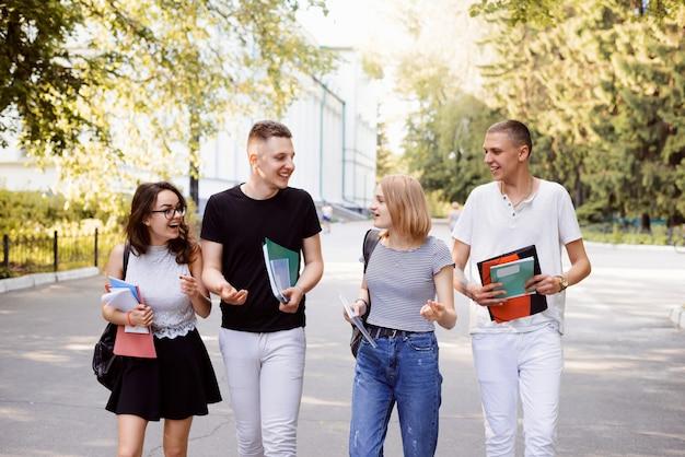 Widok z przodu czterech studentów spacerujących i rozmawiających w kampusie uniwersyteckim, świetnie spędzających czas po zajęciach z przyjaciółmi, rozmawiających razem Premium Zdjęcia
