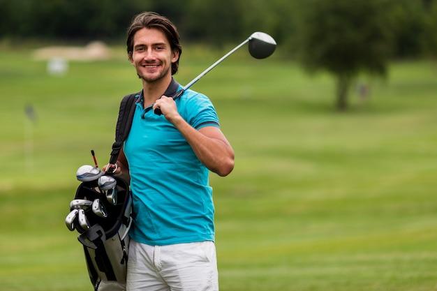 Widok z przodu dorosły człowiek z kijami golfowymi Darmowe Zdjęcia