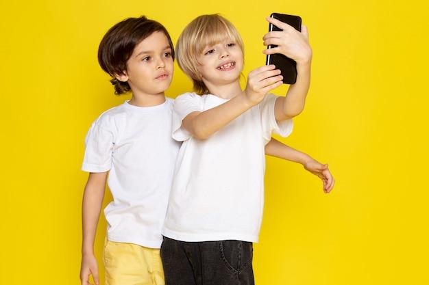 Widok Z Przodu Dwóch Chłopców W Białych Koszulkach Biorących Selfie Na żółtym Biurku Darmowe Zdjęcia