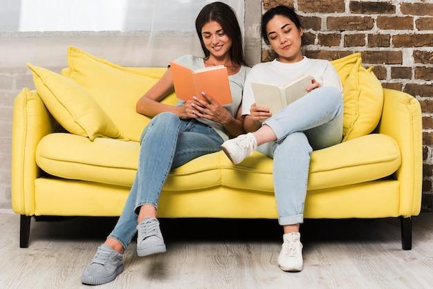 Widok Z Przodu Dwóch Przyjaciół Relaks W Domu Na Kanapie Z Książkami Darmowe Zdjęcia