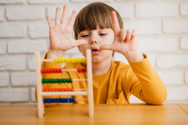 Widok Z Przodu Dziecka Za Pomocą Liczydła, Aby Nauczyć Się Liczyć Darmowe Zdjęcia