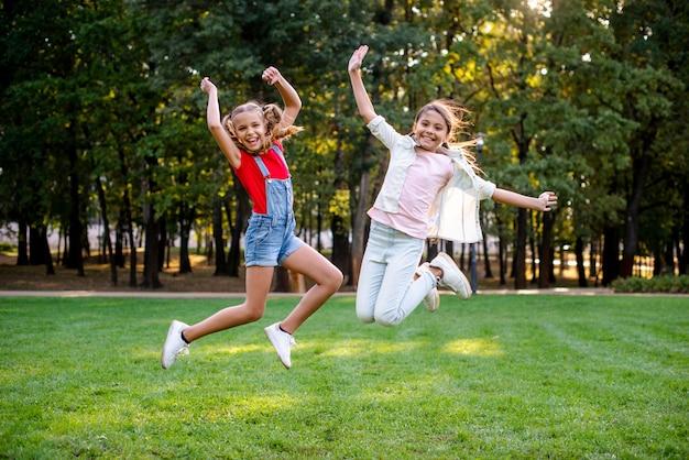 Widok z przodu dziewcząt skaczących w parku Darmowe Zdjęcia