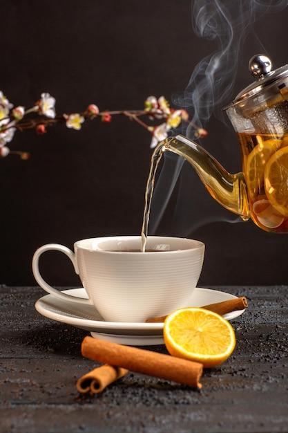 Widok Z Przodu Filiżankę Herbaty Z Cytrynowym Cynamonem I Czajnik Na Szarym Biurku Darmowe Zdjęcia