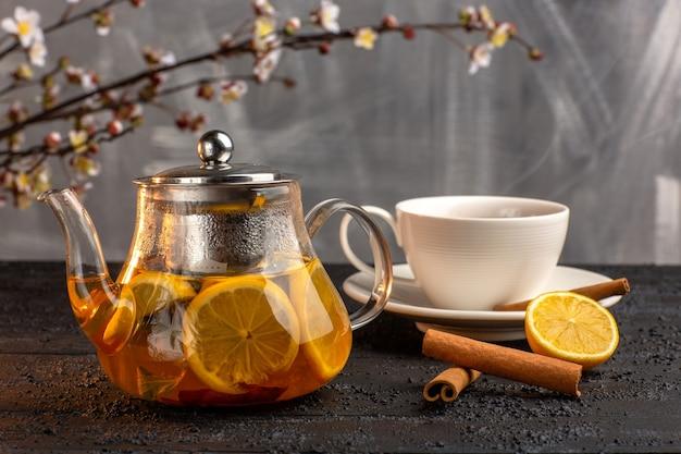 Widok Z Przodu Filiżankę Herbaty Z Cytrynowym Cynamonem I Czajnikiem Na Szarej Powierzchni Darmowe Zdjęcia