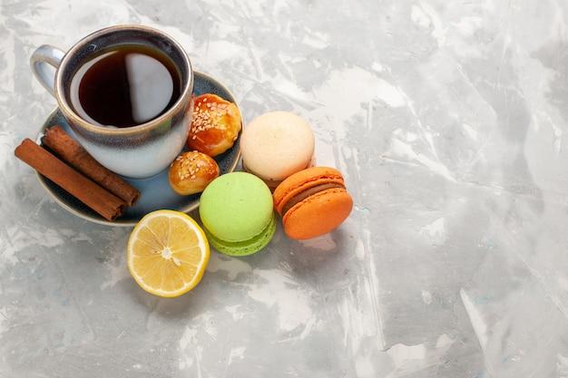 Widok Z Przodu Filiżankę Herbaty Z Makaronikami Cynamonowymi I Ciastkami Na Białej ścianie Herbatniki Słodkie Ciasto Ciasteczka Cukrowe Darmowe Zdjęcia