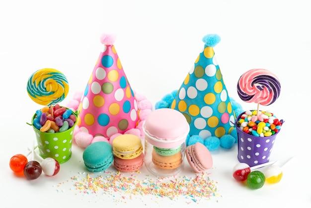 Widok Z Przodu Francuskie Macarons Kolorowe Cukierki I Lizaki Wraz Z Zabawnymi Urodzinowymi Czapkami Na Białym, Uroczysty Kolor Cukru Słodki Darmowe Zdjęcia